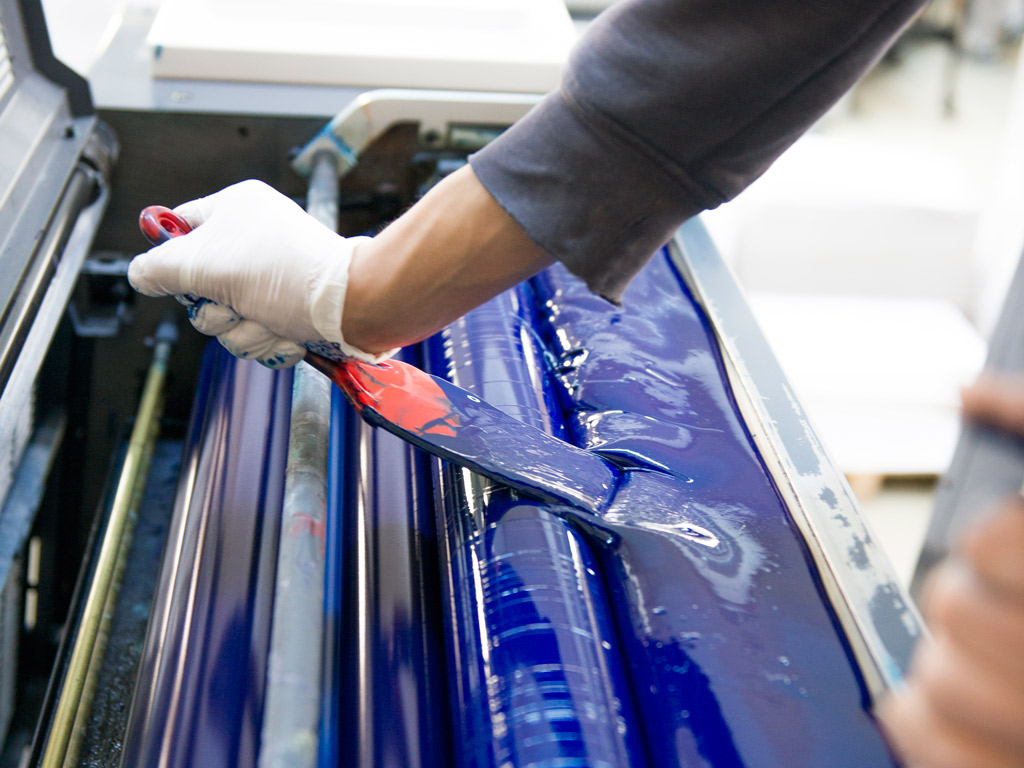 Printing press worker spreading blue ink onto a roller.